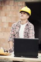 trabalhador carpinteiro com laptop foto