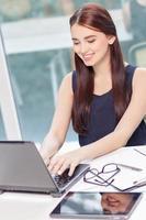 otimista garota sentada com laptop foto