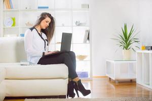 mulher jovem e atraente usando seu laptop em casa foto