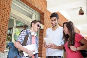 estudantes universitários felizes usando o computador foto