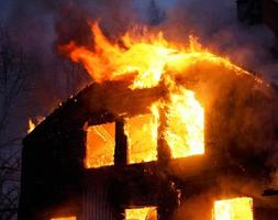 uma casa de madeira em chamas no escuro da noite