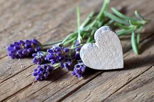 buquê de flores de lavanda e um coração de madeira foto