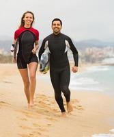 casal com pranchas de surf na praia foto