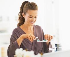 mulher feliz, espremendo creme dental do tubo