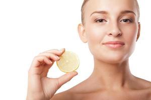 jovem mulher bonita com limão sobre branco foto