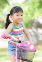 linda garota asiática gosta de andar de bicicleta foto