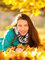 linda garota deitada nas folhas de outono foto