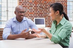 empresários casuais falando na mesa e sorrindo foto