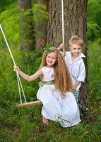 retrato de uma menina menino em uma floresta de verão foto