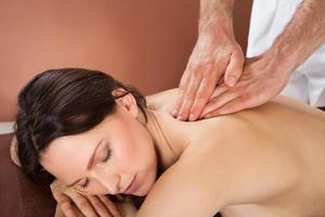 mulher recebendo massagem nas costas em spa foto