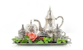 configuração de mesa de chá de férias com folhas de hortelã e flor rosa. foto