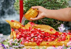 derramando água sobre buddha foto