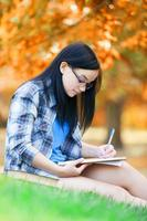 adolescente com notebook no parque. foto
