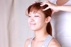 jovem mulher recebendo uma massagem na cabeça foto