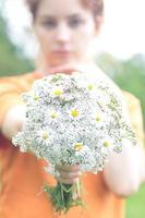 linda menina com um buquê de flores silvestres foto