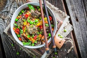 carne com gergelim e legumes frescos com macarrão