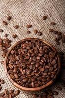 grãos de café em um prato de madeira na bolsa foto