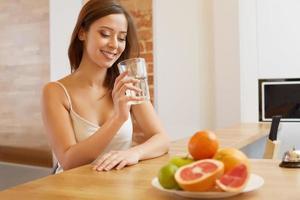 jovem mulher com um copo de água. estilo de vida saudável foto