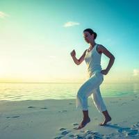 mulher caucasiana, movimentando-se à beira-mar foto