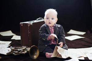 menino caucasiano brinca com trompete foto
