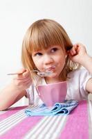 menina tomando café da manhã foto