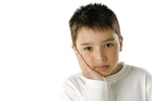 menino caucasiano entediado, descansando a cabeça por lado foto