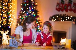 mãe e filha assando pão de gengibre para o jantar de natal foto