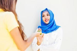 menina caucasiana, esticando uma maçã para mulher muçulmana foto