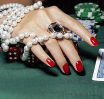 mãos de uma jovem mulher caucasiana com manicure vermelho no cassino
