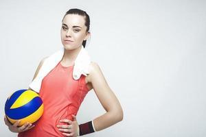 atleta de voleibol profissional caucasiano, segurando uma bola. sobre cinza foto