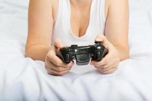jovem mulher caucasiana, jogando videogame na cama foto