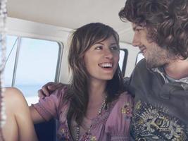feliz casal apaixonado em caravana foto