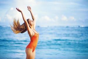 jovem e bela mulher caucasiana com cabelos longos na praia foto