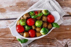 legumes assados berinjela, couve de Bruxelas, tomate manjericão foto