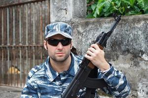 retrato de homem caucasiano militar em guerra urbana, segurando o rifle