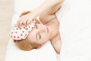 mulher caucasiana para esfriar a cabeça com um travesseiro de água foto