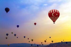 balões de ar quente pôr do sol capadócia foto