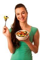 linda mulher caucasiana com uma tigela branca de salada mista foto