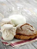 iogurte caseiro, leite e pão em uma mesa de madeira foto