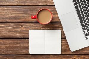 xícara de café e notebook com computador portátil foto