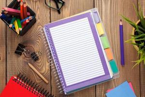 mesa de escritório com flor, bloco de notas em branco e lápis coloridos foto