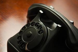 antigo telefone preto retrô com mostrador redondo na mesa de madeira foto