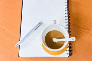 caderno e café em fundo de madeira