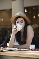 jovem viajante linda curtindo um café no café de rua