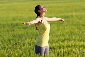 jovem desfrutando a primavera em pé em um campo de cereais