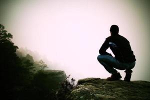 alpinista em posição agachada no pico rochoso e apreciar a paisagem