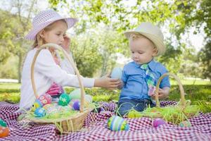 bonito jovem irmão e irmã, desfrutando de seus ovos de Páscoa fora foto