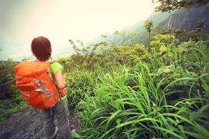 alpinista jovem desfrutar da bela paisagem no pico da montanha foto