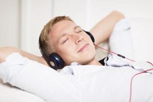 homem sorridente, ouvindo música em fones de ouvido com olhos clo foto