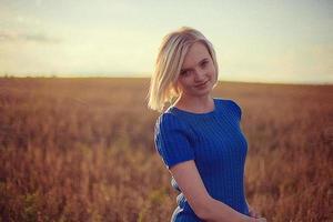linda garota de pé no campo e olhando para a câmera
